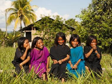 Fem jenter i fargerike klær sitter i gresset utenfor et hus i en landsby