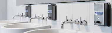 servanter på toalett og såpe dispensere som er merket med etiketter