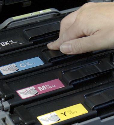 Person putting toner cartridge into a printer