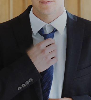 En mann i dress retter på slipset
