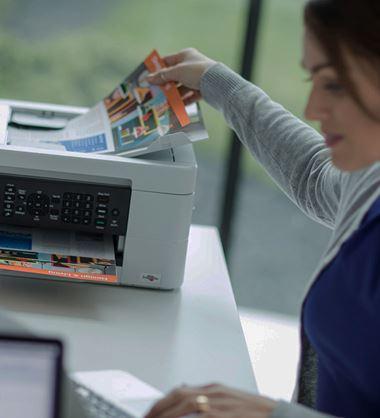 En kvinne sitter ved et skrivebord og plasserer et dokument i dokumentmateren på en printer