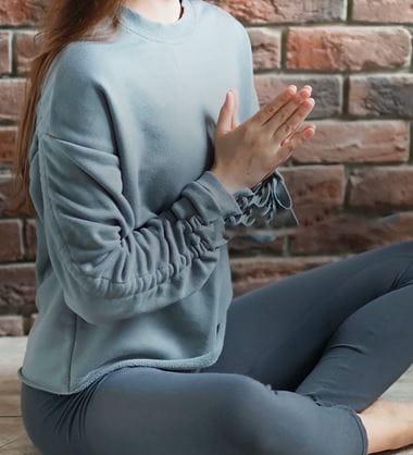 En kvinne sitter på et gulv med bena i kryss og holder hendene sammen