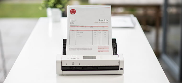 Brother ADS-1700W compact document scanner on desk scanning a document