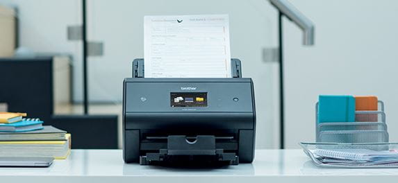 Brother ADS-3600W desktop document scanner on desk with notebooks
