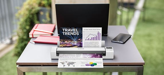 Brother DS-620 Portable document scanner scanning a colour document on table, laptop, orange notebook, mobile phone, grass, outdoors