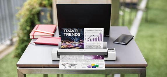 Brother DS620 bærbar dokumentskanner som skanner et fargedokument på et bord, en bærbar PC, oransje notisbok og mobiltelefonligger på bordet som står utendørs med gress rundt