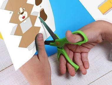 Lapsi leikkaa Creative Centeristä tulostettua askartelutehtävää
