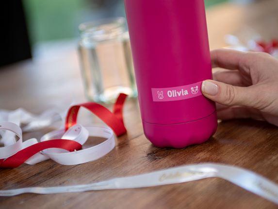 En person fester en Brother P-touch merkelapp med hvit skrift på rosa bunn på en rosa vannflaske. Rødt og hvitt silkebånd ligger ved siden av