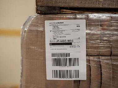 Fire tommers industriell etikett med strekkoder og fraktinformasjon som er skrevet ut på en på en etikettmaskin er festet på en pall med brune esker