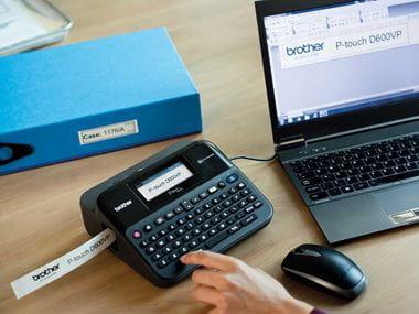 """Patvarus """"P-touch"""" etikečių spausdintuvas ant biuro stalo prijungtas prie kompiuterio"""