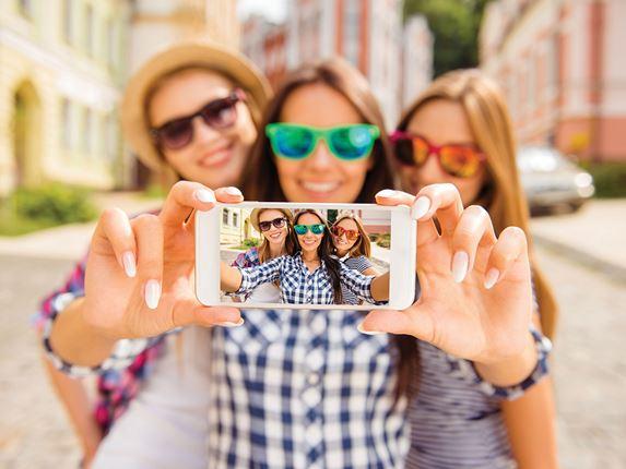 Tre jenter som tar en selfie på en iPhone utendørs