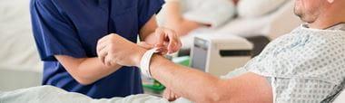 En helsearbeider har skrevet ut og fester et ID-armbånd rundt pasientens håndledd mens pasienten ligger i sengen