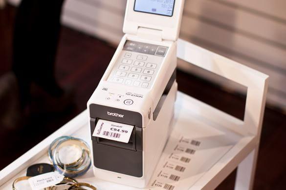 Brotherin TD-2000-sarjan tarratulostin tulostaa viivakoodillista tarraa kuljetuskärryssä