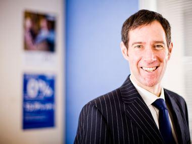 En mann i dress og slips står å smiler