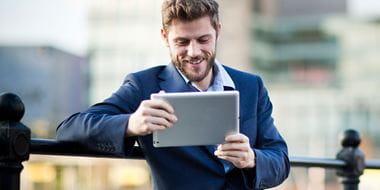 En mann står utendørs og  ser på et nettbrett