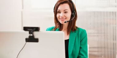 En kvinne i grønn dressjakke og hodetelefoner gir support via datamaskinen