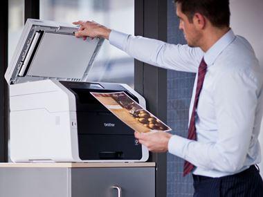 En mann i hvit skjorte og slips åpner lokket til glassplaten på en Brother multifunksjon laserskriver