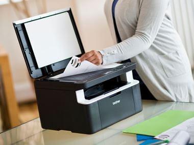 En kvinne kopierer et dokument fra glassplaten på en Brother multifunksjonsmaskin