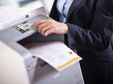 En person trykker på berøringsskjermen til en Brother skriver som skriver ut dokumenter i farger