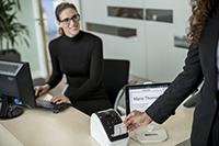 En kvinne med datamaskin skriver ut etikett på en Brother QL810W etikettskriver