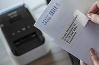 Etikett som er skrevet ut på en Brother QL800 etikettskriver festes på en konvolutt