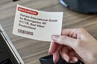 Naisella on punamustana tulostettu osoitetarra kädessään