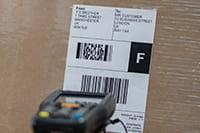 Termisk stregkodelabel på brun boks, der bliver scannet