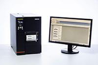 TJ industriell etikettskrivare bredvid datorskärmen