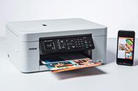 MFCJ497DW spausdintuvas ir mobilus telefonas šalia jo