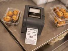 Brother TD-4D etikečių spausdintuvas kepykloje ant metalinio stalo šalia pyragėlių