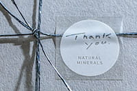 En presang med en merkelapp med hvit logo på klar matt TZe-tape skrevet ut på en på PTP910BT CUBE Pro merkemaskin