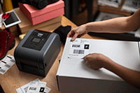 Brother etikettskriver i TD4T-serien med en fraktetikett som plasseres på hvit boks