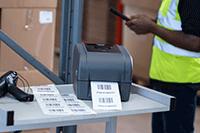 En Brother etikettskriver i TD4T-serien på et metallvogn skriver ut etiketter med strekkoder