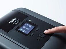En finger trykker på en knapp på en Brother etikettskriver i TD4T-serien med LCD skjerm