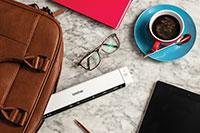 Brother DS640 mobil dokumentskanner på et marmorbord smmen med en skinnveske, briller, kaffekopp,  blyant, nettbrett og en rosa notisbok