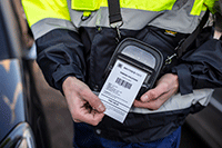 Brother RJ mobil skriver i en skulderstopp bæres av en person i uniform mens han skriver ut en kvittering