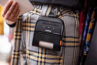 En person i rutet bukse bærer en 3 tommers RJ mobil skriver i en skulderstropp på kroppen