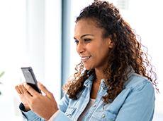 Kvinne som holder smarttelefon for å velge Brother PTP710BTH CUBE Plus merkemaskin fra listen over Bluetooth-enheter