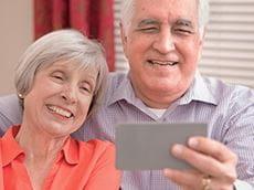 Isovanhemmat katsovat videota lapsenlapsistaan. Video on saatu näkyville skannaamalla Brotherin P-touch-tarraan tulostettu QR-koodi.