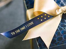 En gave pyntet med et marineblått silkebånd med gull skrift skrevet ut på en Brother PTP710BTH CUBE Plus merkemaskin