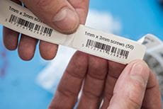 En hånd holder etiketter i fast format med strekkoder
