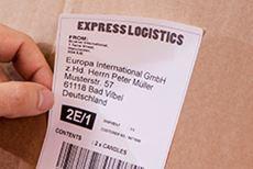 Hånd holder leveranseetikett i bredt format med strekkode