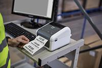 En mann på et lager med en datamaskin som skriver ut etiketter med en Brother etikettskriver fra TD4D-serien