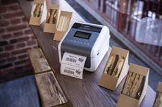 En Brother etikettskriver i TD4D-serien står på en hylle sammen med innpakkede smørbrød med etiketter på