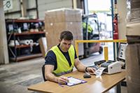 En mann på et lager med en Brother etikettskriver i TD4D-serien som skriver ut en leveranseetikett