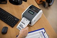Brother TD-4550DNWB stalinis etikečių spausdintuvas ant medinio stalo ir vyro ranka laikanti spausdinamą etiketę