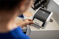 Hoitaja tulostaa potilastietotarraa Brother TD4410D-etikettitulostimella
