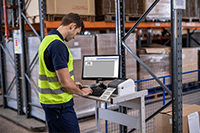 Man wearing hi-vis printing label on Brother TD-4410D desktop label printer in warehouse