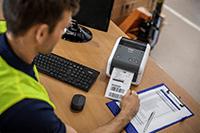 Brother TD-4520 į tinklą jungiamas stalinis etikečių spausdintuvas ant medinio stalo su siuntimo užrašais šalia