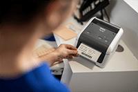 Brother TD4520DN skrivebords etikettskriver på et sykehus med utskrift av en etikett med informasjon om pasienten